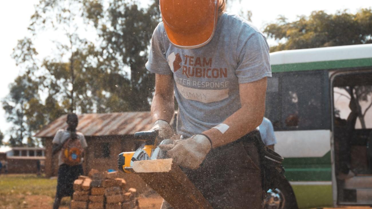Man cutting wood with a saw.