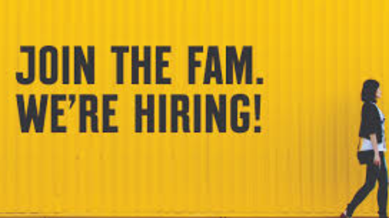 "a yellow image with black text stating ""join the fam. we're hiring!"" with a woman walking beside the image."