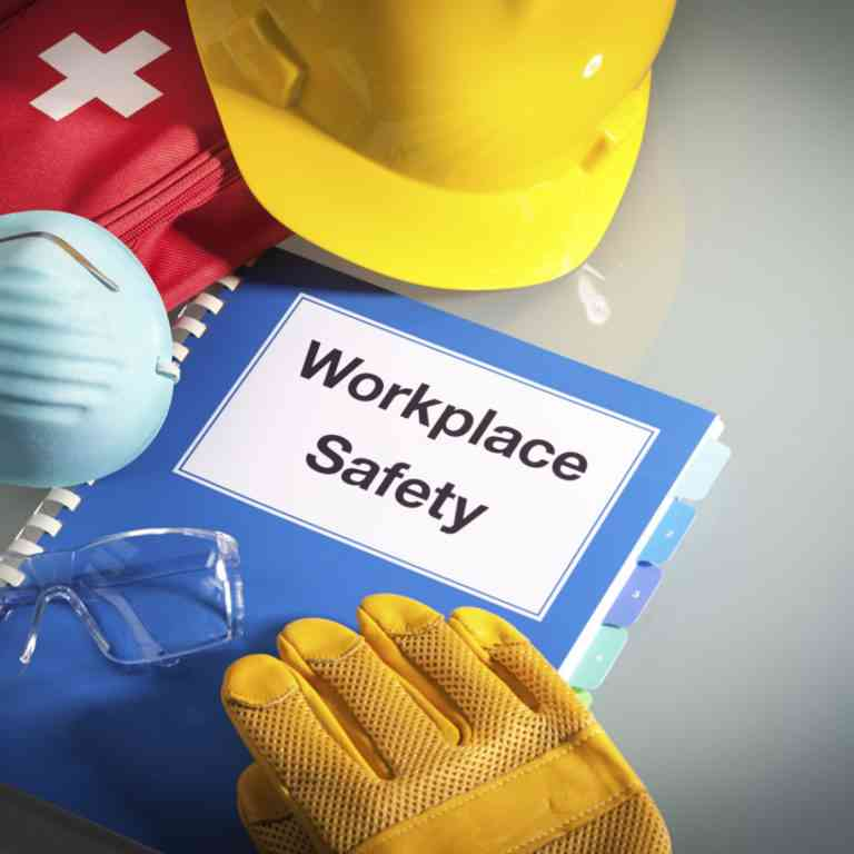 Workplace Safety Handbook with OSHA Requirements next to A First Aid Kit, Respirator Face Piece, Hart Hat, and Safety Gloves